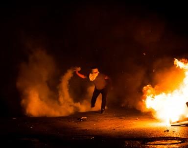 Un manifestant relance une grenade de gaz lacrymogène tirée par les forces de l'ordre